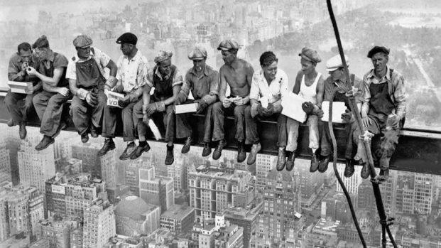Obreros sentados en viga de rascacielos